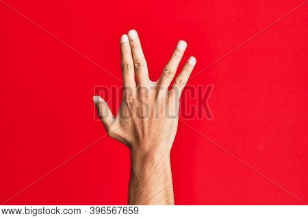 Arm of caucasian white young man over red isolated background greeting doing vulcan salute, showing back of the hand and fingers, freak culture