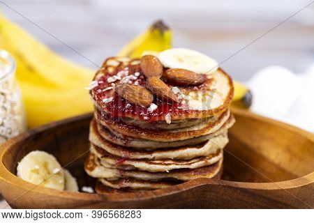 Stack Of Oat Pancakes With Jam And Almonds In A Wooden Plate