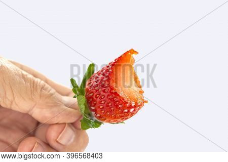Bitten Off Red Strawberry With Green Leaves In Hand Against White Background