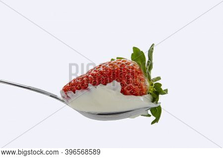Red Strawberries With Green Leaves In A Spoon Of Sour Cream Against White Background