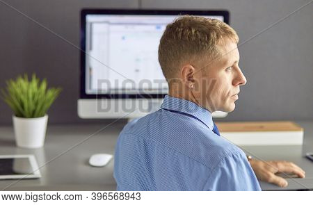 Young Businessman Working In Office, Sitting At Desk, Looking At Laptop Computer Screen, Smiling