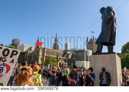 London - September 20, 2019: Statue Of Winston Churchill Surrounded By An Extinction Rebellion Prote