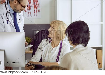 Middle-aged Male Doctor Accompanies The Work Of A Colleague