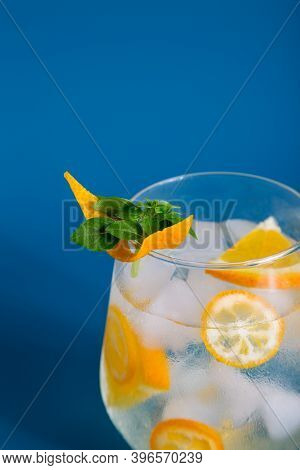 Close Up Glass With Soda Water And Citrus, Garnished With Orange And Basil At Blue Minimal Backgroun