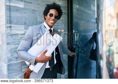 Young handsome african american architect man smiling happy. Standing with smile on face holding blueprints at the office door.