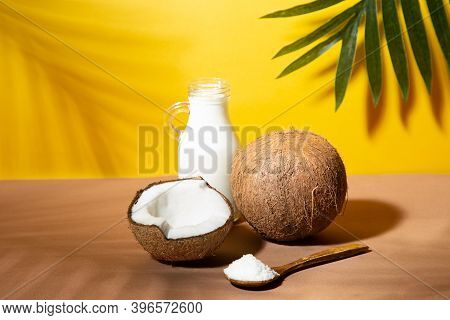 Coconuts, Coconut Milk And Shredded Coconut On Yellow And Brown Background With Palm Shades.
