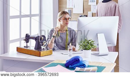 Beautiful Young Girl In A Factory With A Sewing Machine At The Table