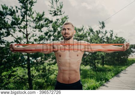 Horizontal Shot Of Sporty Man With Bare Chest Exercises With Elastic Expander, Gains For Strong Musc