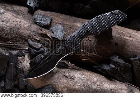 Knife With A Curved Blade. Black Knife On A Log.