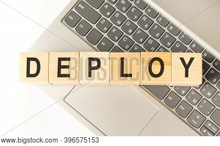 Word Deploy. Wooden Cubes With Letters Isolated On A Laptop Keyboard. Business Concept Image.