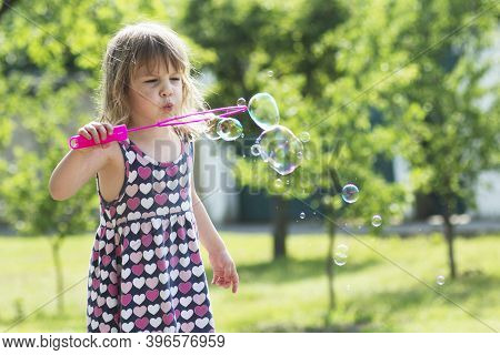 The Cute Little Girl In Dress Is Blowing Soap Bubbles Outdoors.