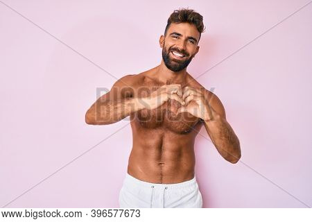 Young hispanic man standing shirtless smiling in love doing heart symbol shape with hands. romantic concept.