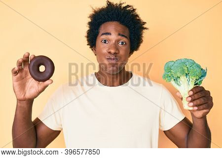 Handsome african american man with afro hair holding broccoli and chocolate donut puffing cheeks with funny face. mouth inflated with air, catching air.