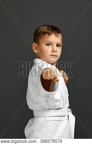Portrait Of Little Child Boy In A White Karate Kimono Over Gray Background. Karate Fighter Ready To