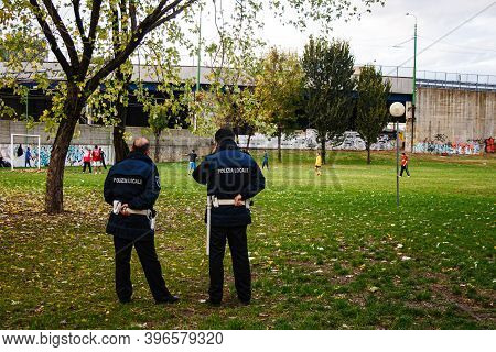 Milan, Italy - November, 05: Two Italian Traffic Wardens Observe The Migrants Playing Soccer In The