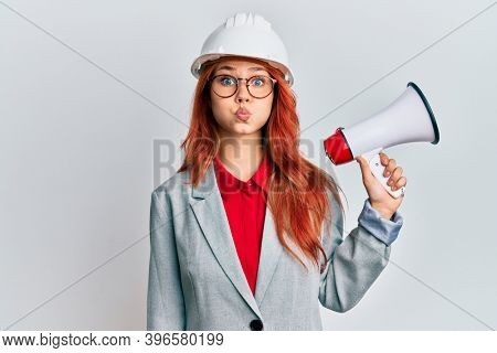 Young redhead woman wearing architect hardhat and megaphone puffing cheeks with funny face. mouth inflated with air, catching air.