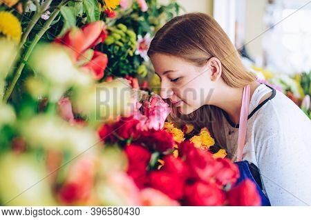 Young Florist Smelling Beautiful Fresh Flowers In A Flower Shop.