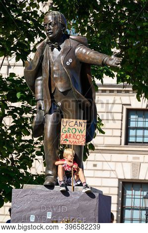 London - September 20, 2019: Young Boy Sitting On A Statue Of David Lloyd George, In Parliament Squa