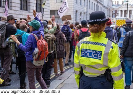 London, Uk - October 18, 2019: A Police Officer Walks Alongside An Extinction Rebellion Protest In L