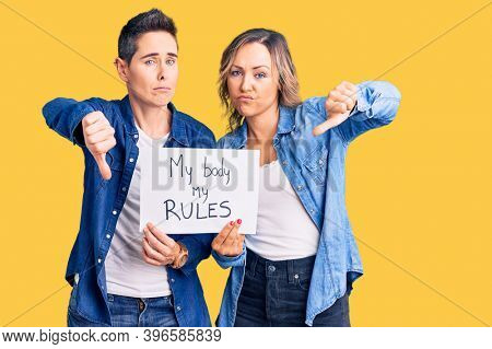 Couple of women holding my body my rules banner with angry face, negative sign showing dislike with thumbs down, rejection concept