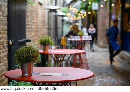London - September 30, 2019: A Row Of Empty Tables On A Cobbled Street In An Outdoor Dining Area Of