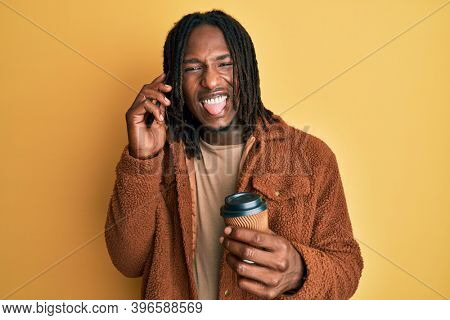 African american man with braids having conversation talking on the smartphone sticking tongue out happy with funny expression.
