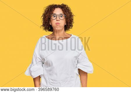 Beautiful middle age mature woman wearing casual clothes and glasses puffing cheeks with funny face. mouth inflated with air, crazy expression.