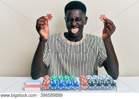 Young african american man playing poker holding casino chips sticking tongue out happy with funny expression.