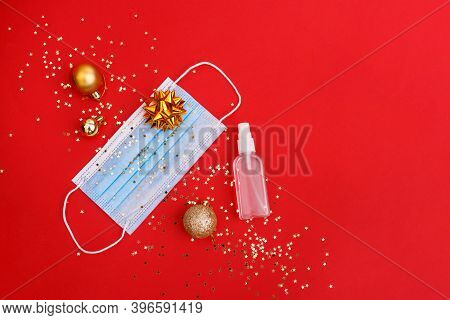 Medical Mask And Antiseptic, Christmas Decorations On Red Background With Stars Confetti. Medical Pr