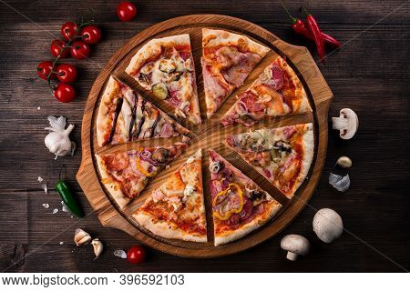 Different Pizza Slices On A Round Wooden Board, Slices Of Pizza With Different Toppings On A Wooden