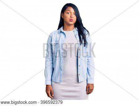 Hispanic woman with long hair wearing casual denim jacket puffing cheeks with funny face. mouth inflated with air, crazy expression.
