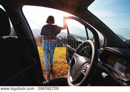 girl near the car and a beautiful mountain landscape in the background. Roadtrip