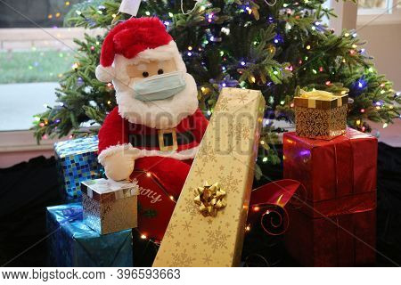 Coronavirus Christmas. Santa Claus wears a Paper Face Mask with Presents in front of a Christmas Tree decorated with Paper Face Masks as Ornaments to help avoid the Coronavirus. Covid-19 Christmas.