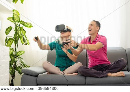 Young Funny Couple Playing Video Games Virtual Reality Glasses In Their Apartment - Happy People Hav