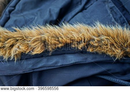 Brown Fur On The Hood Of A Black Fabric Jacket