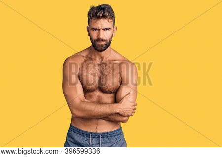 Young hispanic man wearing swimwear shirtless skeptic and nervous, disapproving expression on face with crossed arms. negative person.