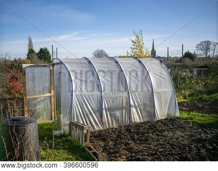 Outdoor Transparent Pvc Greenhouse With Open Door  At The Foot Of Plowed And Sown Land On A Sunny Da