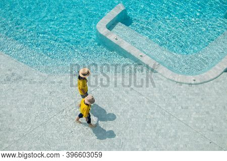 Summer Vacation And Travel Trip Concept : Woman And Girl Wear Weave Hat And Walking Relax In Pool.