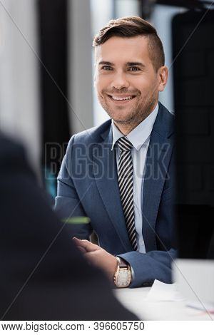 Businessman Sitting At Workplace With Blurred Co-worker On Foreground