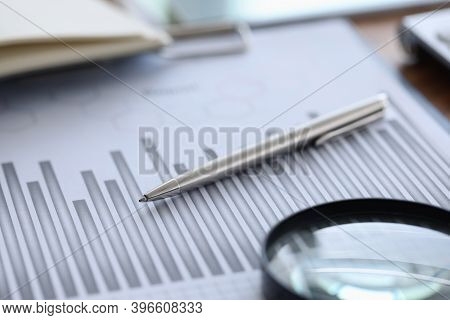 Ballpoint Pen And Magnifying Glass Lying On Documents With Graph In Office Closeup. Dynamics Of Econ