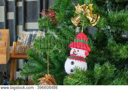 Winter Christmas Background Concept : Snow Toy Hang On Green Pine Tree.