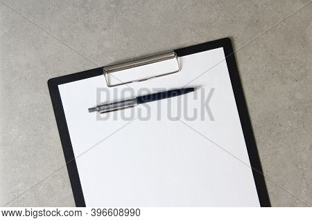 Template Of White Paper With A Ballpoint Pen On Light Grey Concrete Background In A Black Tablet Wit