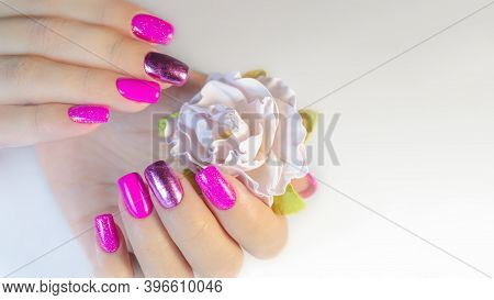Hand Of A Young Woman With A Manicure In Pink Tones And A Flower On A White Background. Manicure Ide