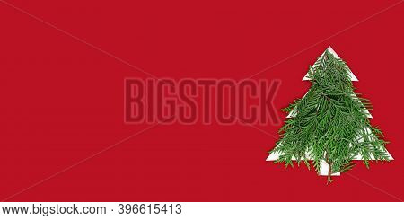 Christmas Tree Cut Out Of Paper On A Red Background. Silhouette Of A Christmas Tree With Green Fir B