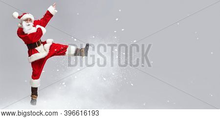 A jolly young man dressed as Santa Claus jumps and playing pranks with snow. Merry Christmas and Happy New Year! Copy space.