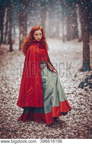 Christmas tales. A beautiful red-haired girl of the Middle Ages walks through the winter forest. Celtic culture. Fantasy world.