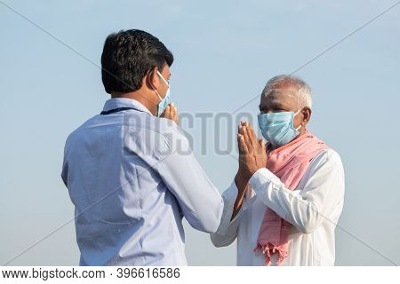Low Angle View, Farmer Greeting To Banker Or Corporate Government Officer By Doing Namaste While Bot