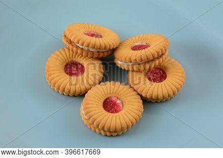 Strawberry Creme Filled Sandwich Cookies With Strawberry Jam On Top On Blue Plate