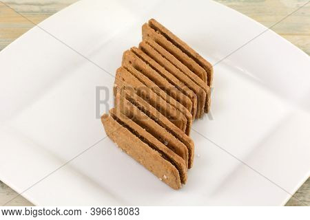 Stack Of Chocolate Creme Filled Sandwich Cookies On White Snack Plate