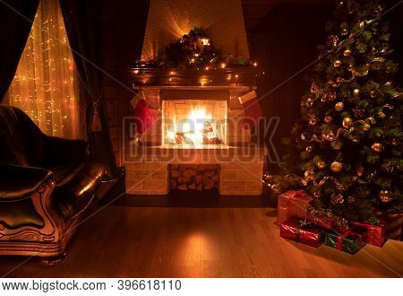 Christmas decorated tree in dark interior with fireplace, armchair, and window